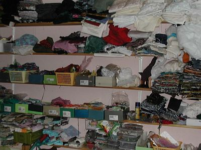 lots of shelves with fabric on including lots of white fabric for dyeing in the top right hand corner