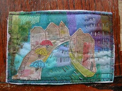 fabric postcard with layered sheers in blues, purples, greens and houses painted and appliqued