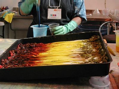 yellow, red and brown dyebath with pleated fabric in tray