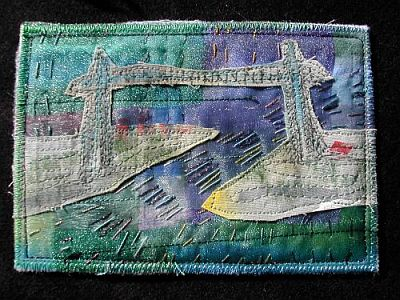 purple/blue/grey fabric postcard featuring bridge over river