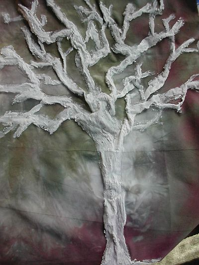 white tree emerging from green fabric