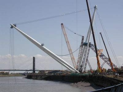 lots of uprights and cranes around a new bridge going up