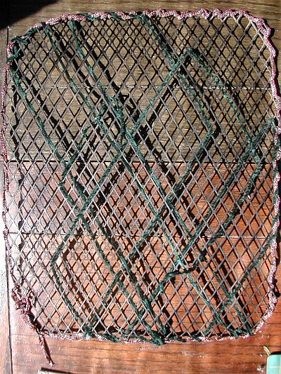 iron grid from barbecue, wrapped with green and reddy silver thread